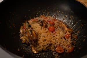 Noodles stirred in frying pan