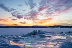 A photo of sunrise breaking over a frozen Hudson River on a February morning.