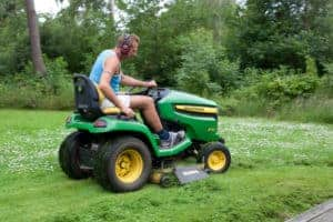 guy on a john deere riding lawn mower