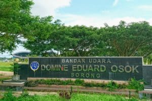 Sign of Domine Eduard Osok Airport Sorong and the airport building in the background