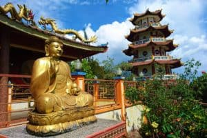 Meditating Golden Buddha in front of the Temple, Pagoda in the background