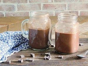 red wine hot chocolate in mugs on wooden table with blue napkin