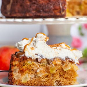 slice of apple caramel cake with diced apples and whipped cream topping