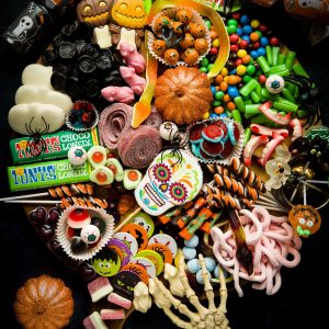 A Platter filled with Halloween sweets, candy and chocolate. There is a skeleton hand reaching in at the bottom of the platter.