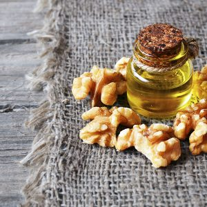 Walnut oil with peeled walnuts on burlap cloth background.Healthy eating,therapeutic and bodycare concept.Selective focus.