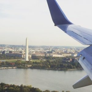 photo outside plane window with wing and george washington memorial in background