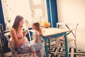 mother and daughter sitting at kitchen table in painted room