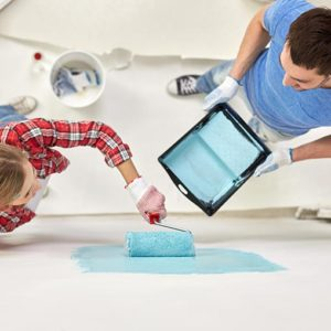 husband and wife painting a wall blue