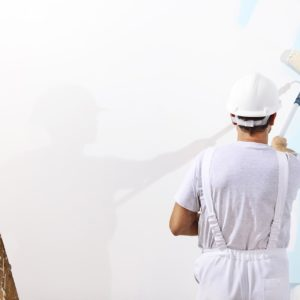 painter rolling white paint on blue wall