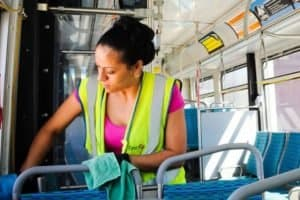 A woman sanitizing seats on a bus