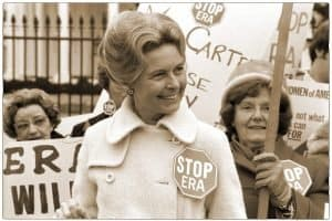 Two smiling women hold Stop ERA signs behind a woman in a white coat with a STOP ERA button.