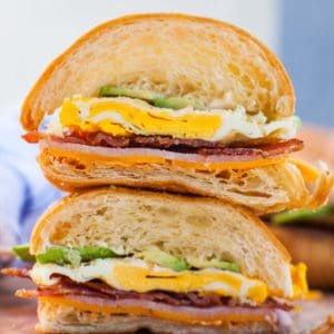 close up of sliced breakfast croissant sandwich with bacon and egg