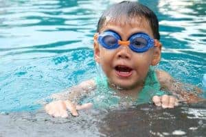 kid with goggles in the swimming pool