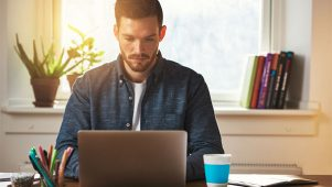 Why employing freelancers boosts business productivity - Freelancer busy working, sat in front of desk and laptop.