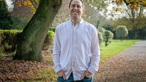Starting a freelance consulting business during a pandemic - Communications Consultant Michael Rosen smiling, stood in the park.