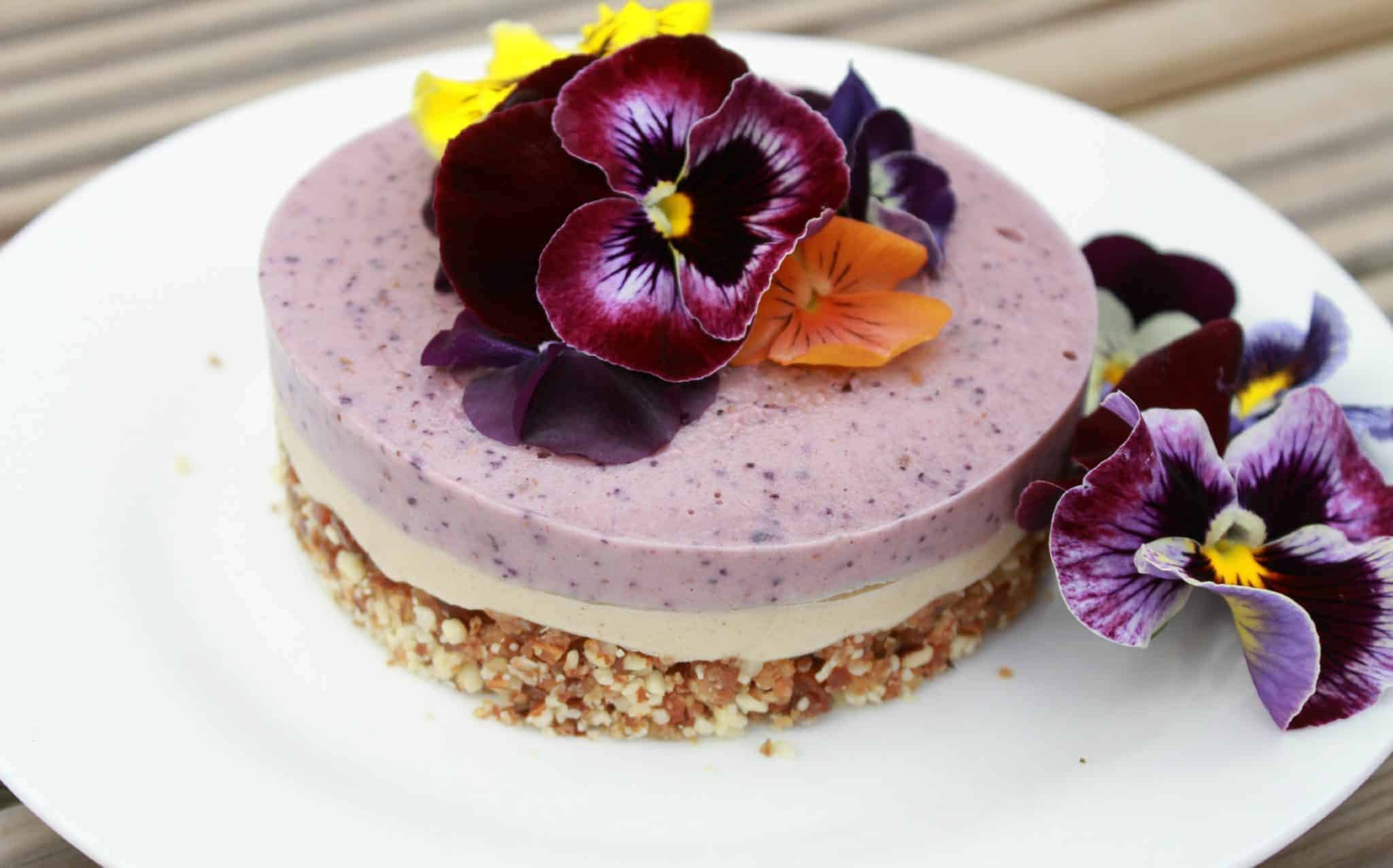 A beautiful raw berry cheesecake decorated with edible flowers from Amy at Mr and Mrs T Plus Three