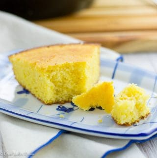 Close up of a single slice of cornbread with the end broken off.