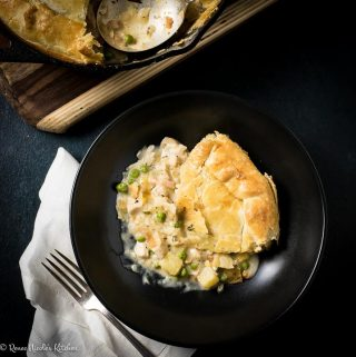 Overhead square image of a serving of homemade chicken pot pie with tarragon gravy in a black bowl next to a white cloth napkin.