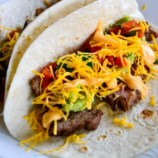 Steak Tacos with guacamole, salsa, shredded cheddar, and spicy srirach sauce PIN