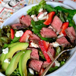 Feature image for California steak salad: loaded with tender steak, crunchy greens, juicy strawberries, tangy goat cheese, and topped with a bright, zingy citrus vinaigrette.