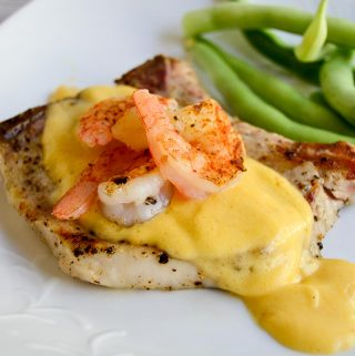 Bone in pork chops and succulent shrimp pair with an amped-up hollandaise sauce for a fun spin on summer grilling in this Grilled Pork Chop Surf and Turf.