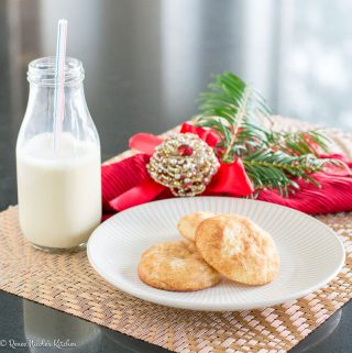 Three cookies on a white plate next to a festive napkin and jar of milk.