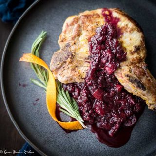 Close up, square image of a bone in pork chop on a gray plate with a spring of roemary and strip of orange zest to the side, topped with blackberry applesauce.