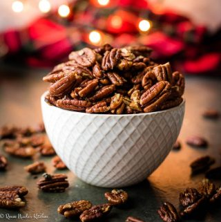 Close up shot of brown butter roasted pecans in a white dish on a dark gray background with red plaid and Christmas lights in the background.