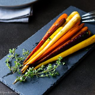 Heirloom carrots on a slate board garnished with thyme.