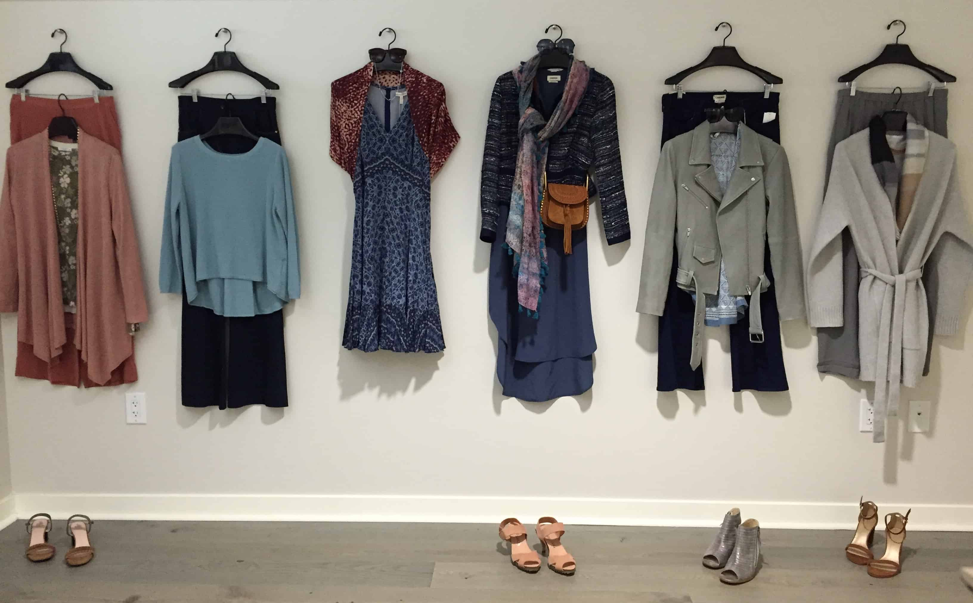 six women's outfits hanging on a wall