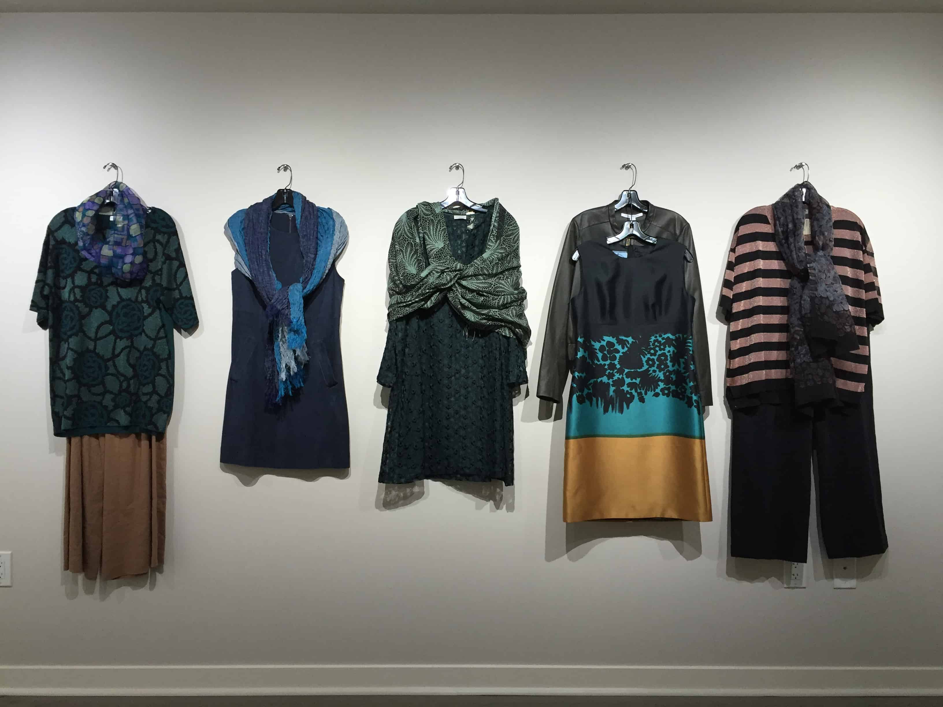 five womens' outfits hanging on a wall