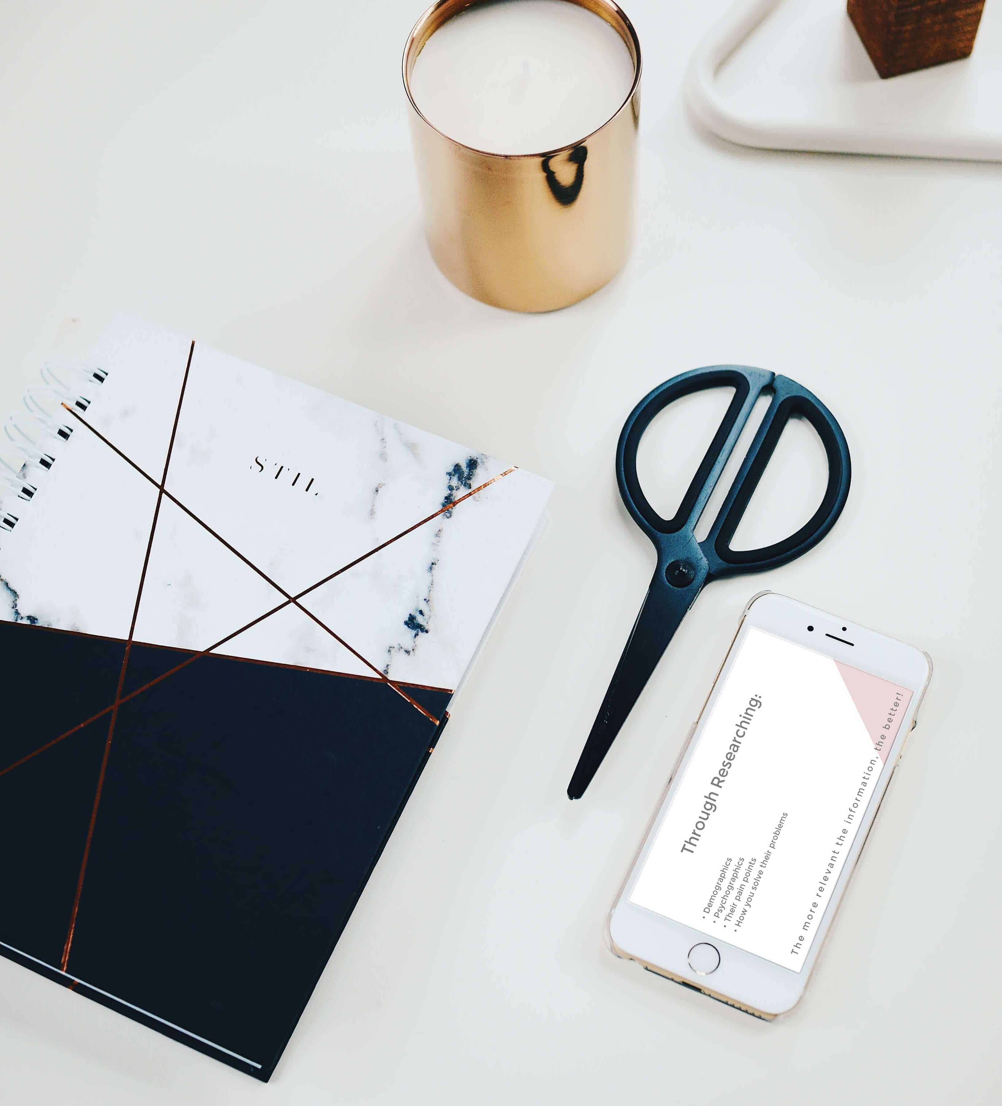 Styled photo of candle, notebook, scissors and iPhone on a desk