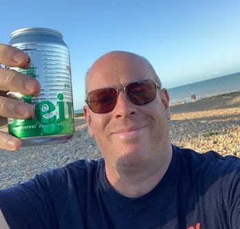 On the beach drinking beer.