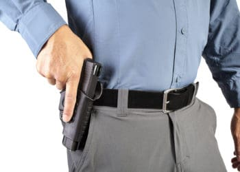 Man holding his hand on a holstered pistol