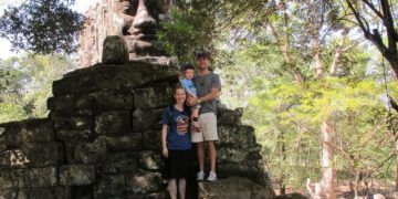 The family at the north gate of angkor wat, siem reap's most famous ruined temple.