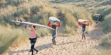 Carrying surfboards through the heather in wales