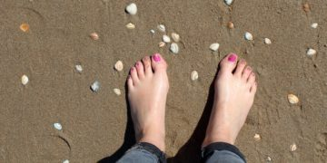 Feet on a beach with pink toenails