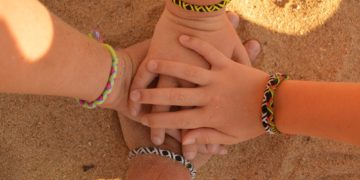 4 hands with friendship bracelets come together the way a blended family does on a familymoon