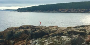 A girl jumps along boulders on the coast of acadia national park
