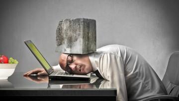 Mann vor Laptop mit Stein auf dem Kopf