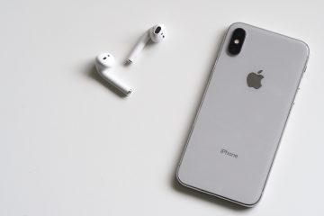 Image of new iPhone laying face down on a white table with earpods next to it.