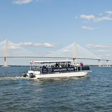 Sandlapper Tours boating off on one of their adventures with the bridge in the background. Boat charter Charleston SC