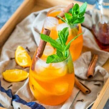 2 drinks with cinnamon sticks and pieces of orange
