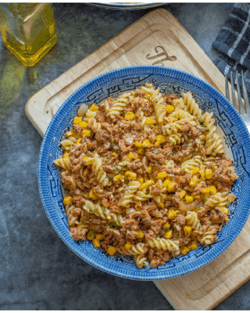 a bowl of tuna and pasta with sweet corn in a blue bowl