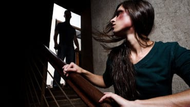 Battered woman escaping from man silhouetted at the top of the stairs, in fear of more violence