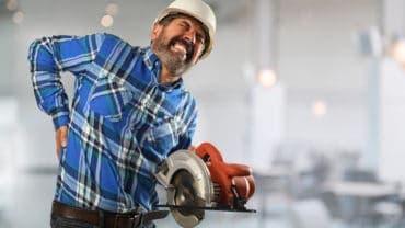 Senior Hispanic worker suffering back injury inside building
