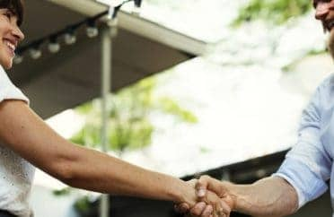 Business woman and man shaking hands and smiling