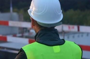View of construction worker at Hinkley, wearing safety helmet and high visibility jacket