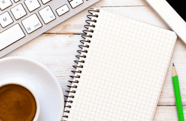 Photo of keyboard, coffee, notebook, pencil and tablet on a desk
