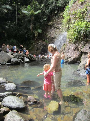 A mom and daughter explore the pools beneath a waterfall in Puerto Rico's El Yunque national forest.